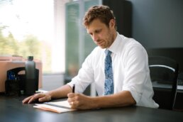 A man sitting a desk writing on a legal pad